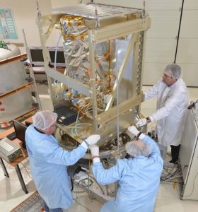 Men in lab coats, hairnets and white gloves holding onto a large metal structure