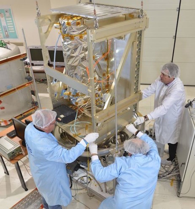 Men in lab coats, hairnets and white gloves holding onto a large metal structure.