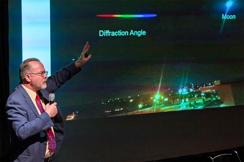 Man with microphone pointing to diagram of light spectrum on big TV screen.