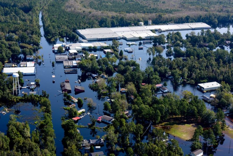 Aerial view of flooded landscape, blue water surrounding half-submerged buildings.