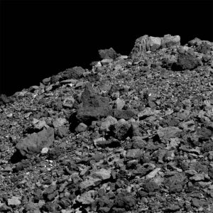 Hill covered with gray rocks and boulders. Black sky.