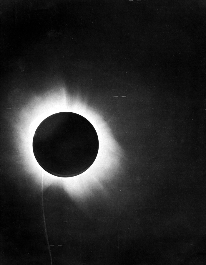 Black circular silhouette of moon, surrounded by solar corona, during a total solar eclipse.