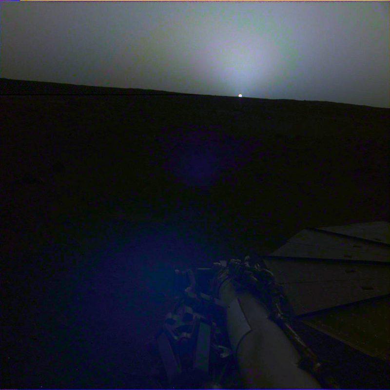 Tiny bright half circle on horizon of nearly set sun, blue twilight sky.