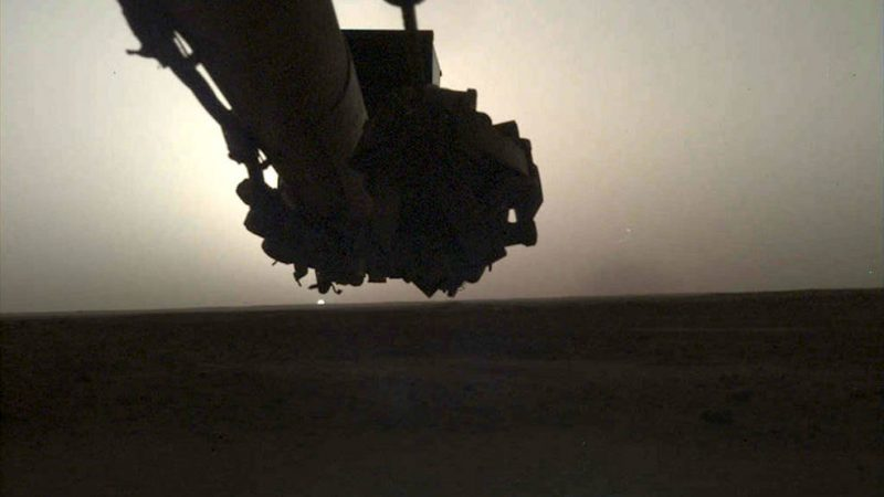 Sunrise with tiny sun beneath silhouette of lander's arm.