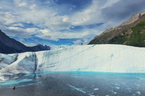White wall of ice next to bright blue water.