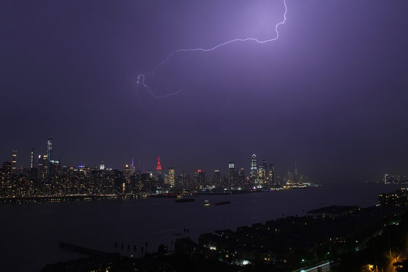 Night lightning over colorfully lit NYC skyline beyond wide waterway.