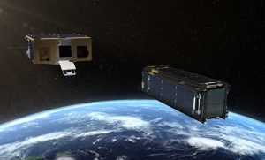 Two box-shaped cubesats above the curve of Earth.