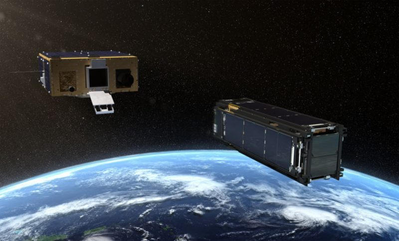 Two box-shaped cubesats above the curve of Earth, the larger one with an open door.