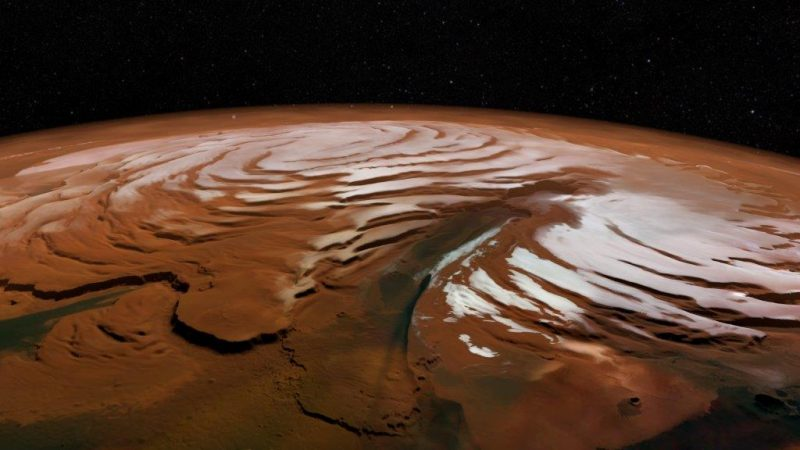 Red liquidy-looking layers like terraces on part of Mars, viewed from orbit, black background.