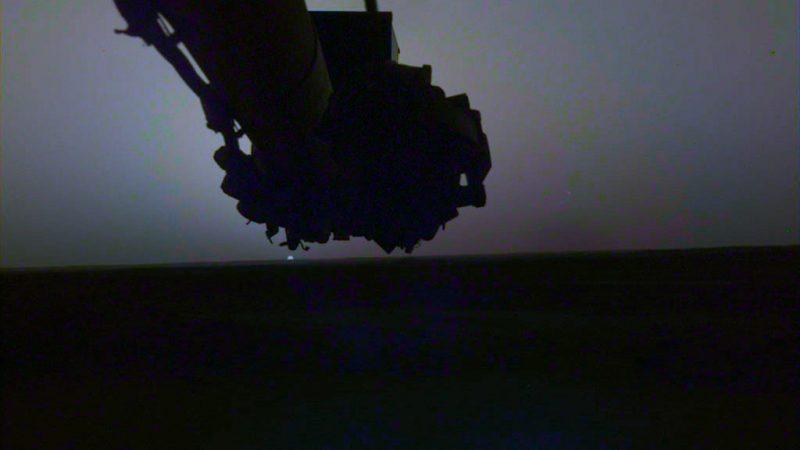 Sunset with tiny sun under lander's arm.