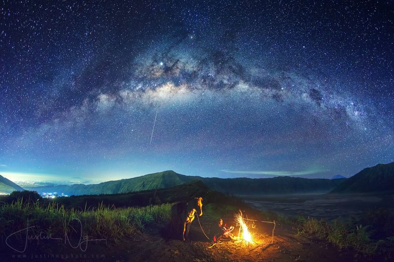 Arc of Milky Way, campfire with man, bright streak in sky, mountainous landscape.