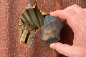 Hand holding a small, dark, irregular meteorite over hole in doghouse roof.