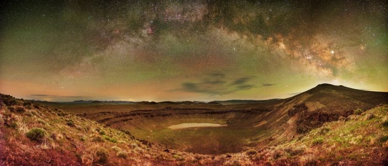 Starry arc of Milky Way over a large desert crater.