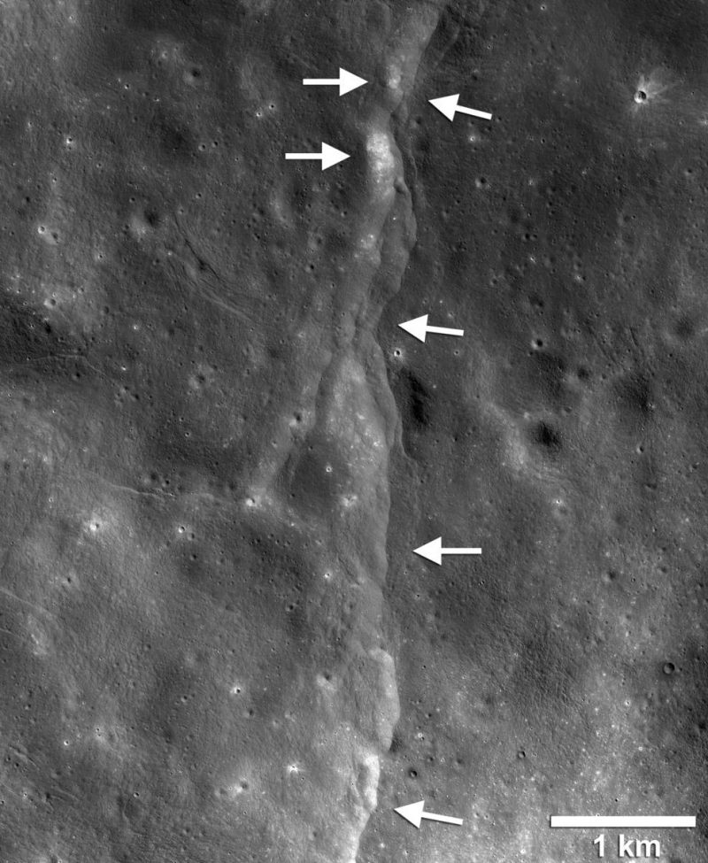 Lunar landscape from orbit with a lighter line down the middle. Arrows point to spots along the line.