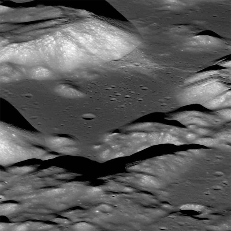 Gray and white pattern of irregular hills, with smaller black shadows and craters.