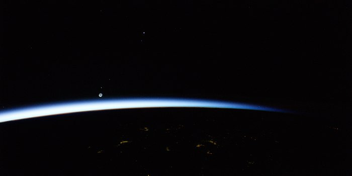 A thin blue-white arc across a black background with two bright dots near edge.