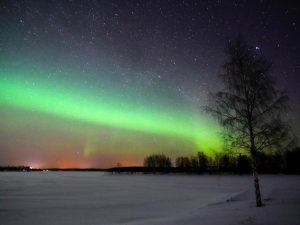 Snowy night landscape with a bright green light across the sky.