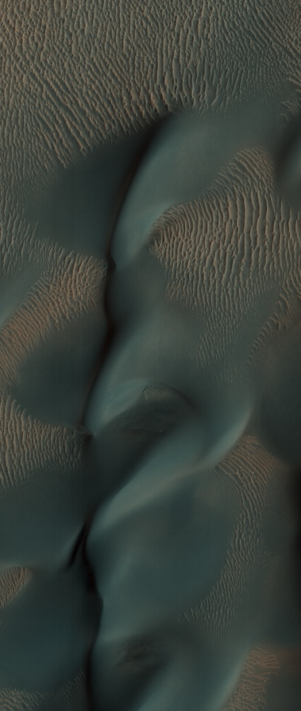 Orbital view of bluish wavelike formations against more normal striped dunes.