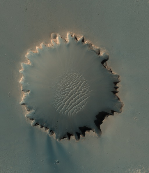 Orbital view of round field of dunes in center of irregular-edged crater.