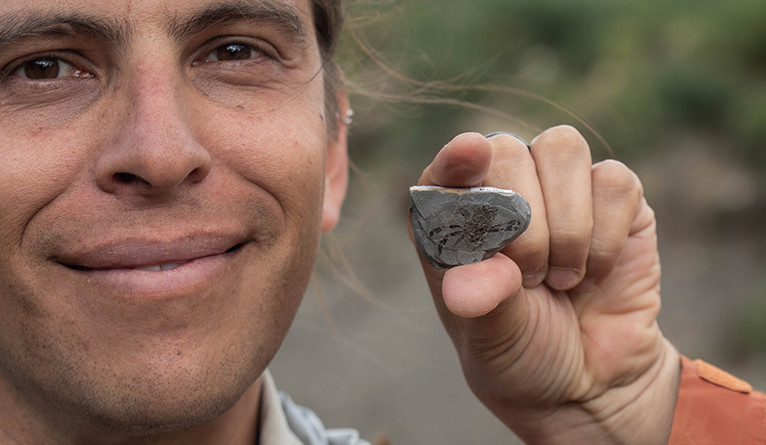 Smiling scientist holding rock with small fossil crab visible on flat side.
