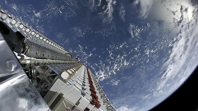 View from a camera mounted at the top of the rocket, looking down at a stack of 60 satellites, with Earth below.