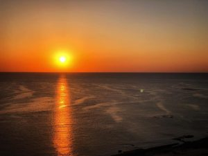 Yellow ball of the sun in an orange sky, reflected in dark purple ocean waves.