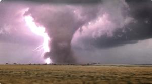 A large, backlighted tornado moving across the Oklahoma prairie.