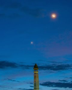Waning crescent moon with earthshine, Venus and fainter Mercury, in a twilight sky.