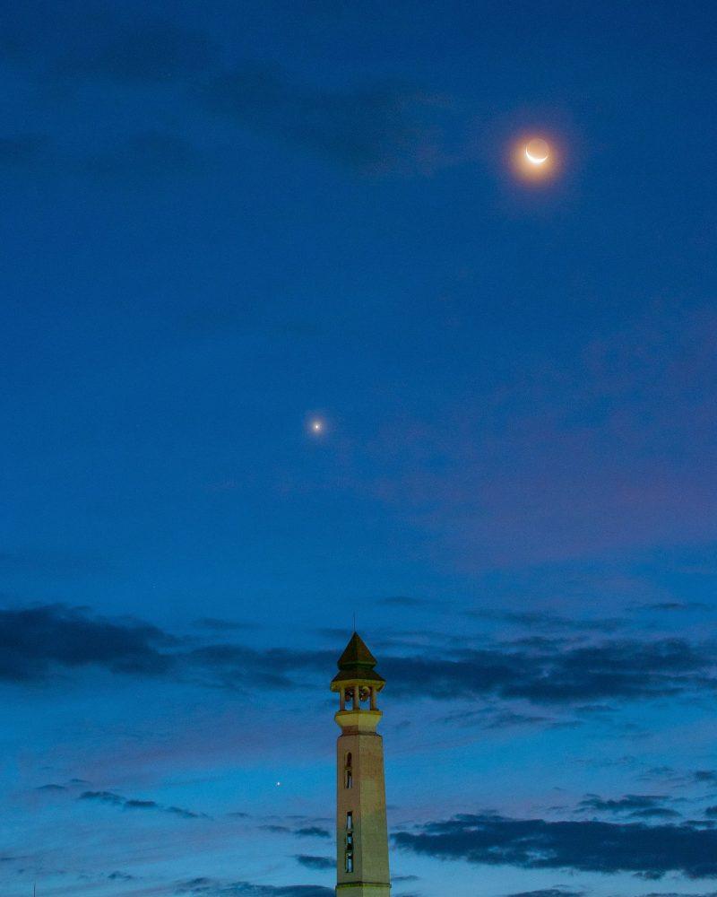 Waning crescent moon, earthshine, Venus & fainter Mercury, in twilight sky near a slim tower.