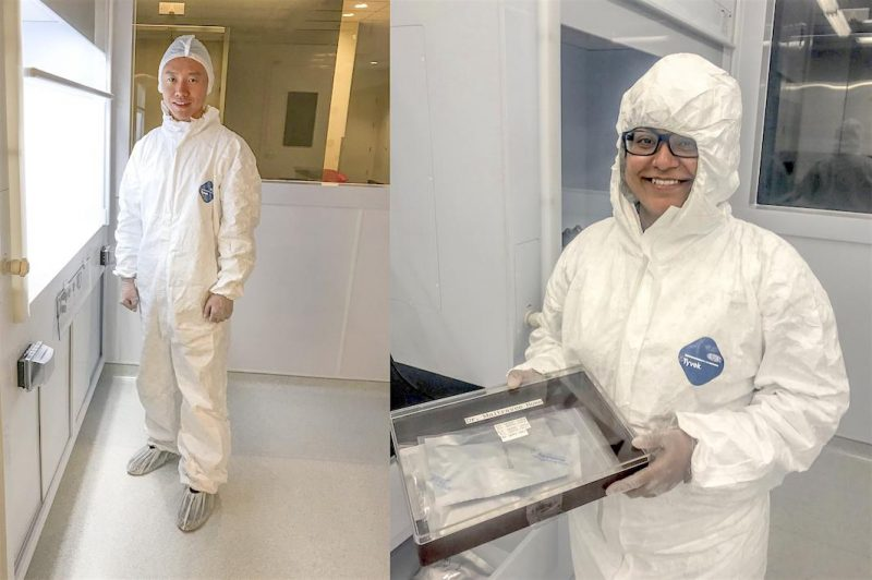 2 grinning scientists in white protective suits, one holding a glass-topped sample box.