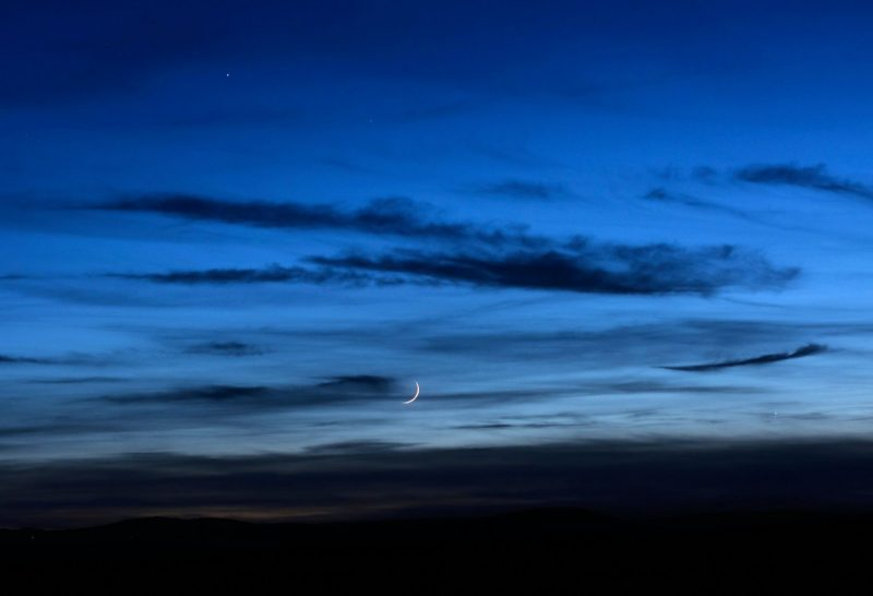 Twilight sky, clouds running left to right, very thin, low crescent moon, two bright dots.