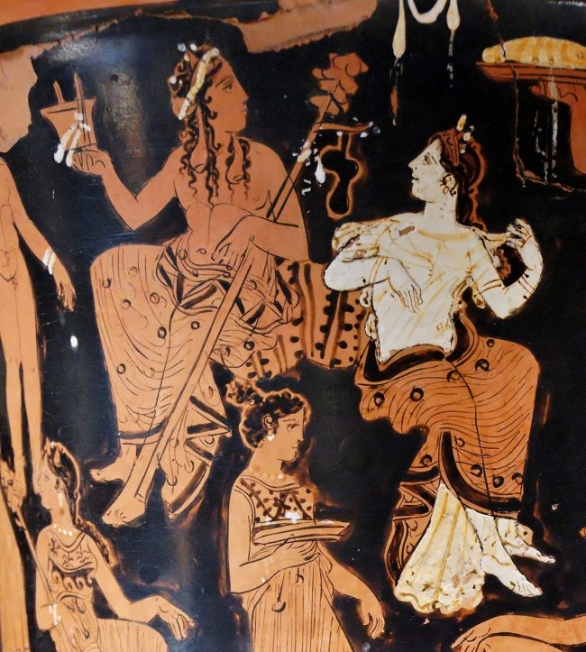 Seated man and woman in Grecian garb painted in red, white, and black on pottery.