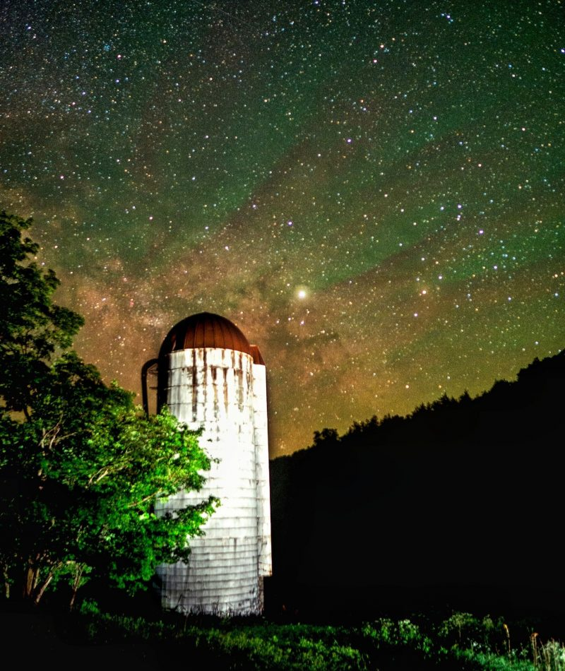 Tall white silo with rusty dome against starry green glowy sky, tree in foreground, hill in background.