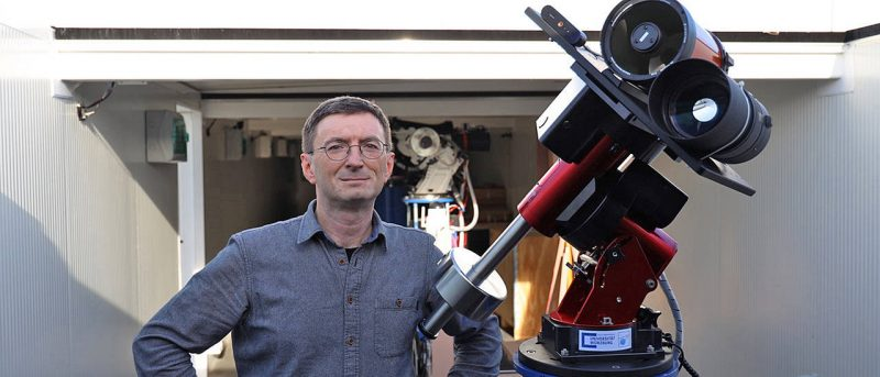 Man with double telescope standing in front of big white box-like structure.