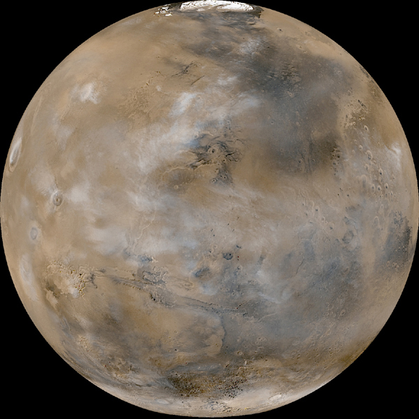 Tan planet with darker markings and patches of white clouds seen from orbit.