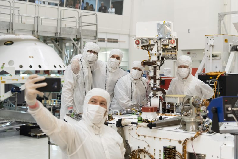 Five engineers in clean-room garb gather around Mars j2020 rover's newly installed mast.