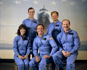 One woman and four men in blue flight suits, with space shuttle in background.