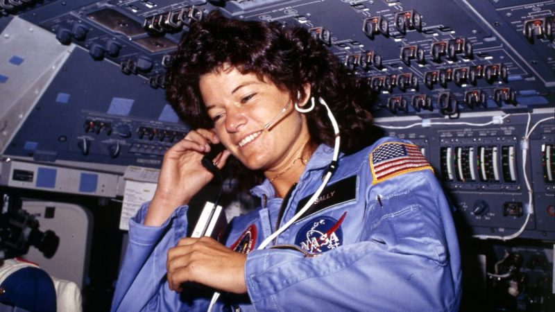 Woman with plentiful curly hair, wearing blue astronaut outfit and headphones, in spacecraft cockpit.