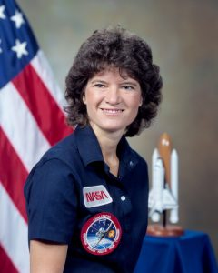 Smiling woman in dark shirt with NASA patches, with model of space shuttle and American flag.