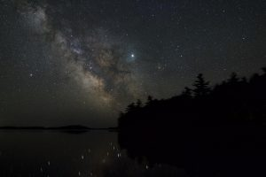 Fuzzy band of Milky Way with bright star over forested lake point