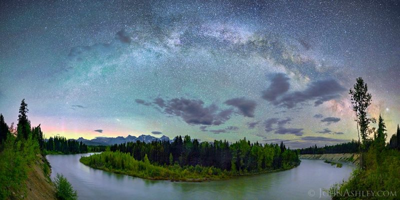 Wide symmetric image of Milky Way arcing over a river, tiny fuzzy oval at left, bright dot to right.