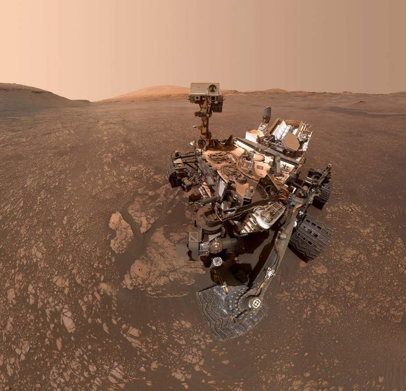 Red Mars landscape, pink sky, complicated machine on wheels.