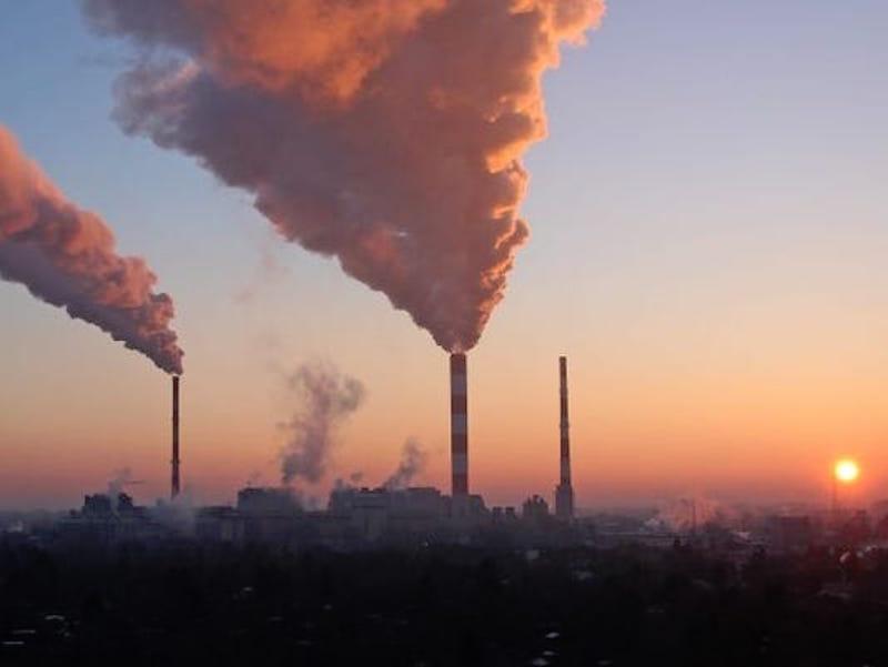 Smoke billowing from two tall, thin smokestacks as sun sets at dusty horizon.