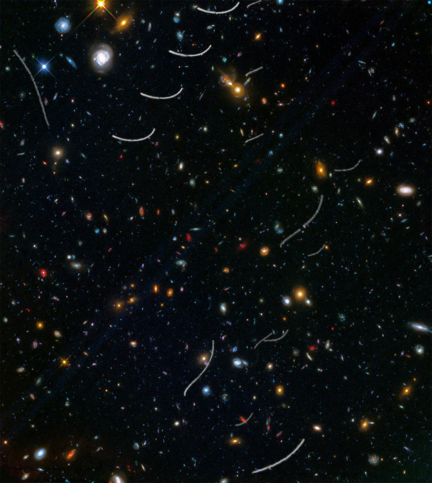 Field of many small colorful galaxies and short threadlike asteroid trails.
