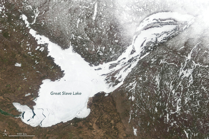 View from space of irregular, ice-covered Great Slave Lake against mostly brownish surface.