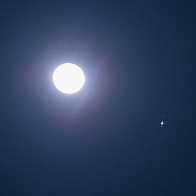 Bright full moon, bright dot of Jupiter nearby, 4 pinpricks of light aligned with Jupiter's equator.