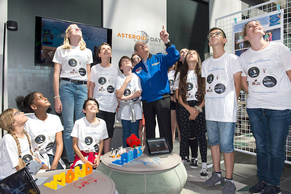 Bunch of children and teens in logo t-shirts looking up in a tall well-lit room.