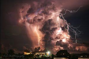 Big dark pinkish gray cloud and lightning bolt in night sky.