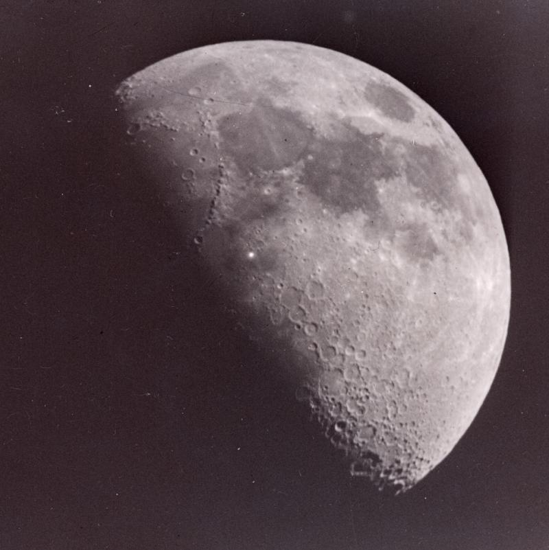 Bright spot on quarter moon near edge of light side.