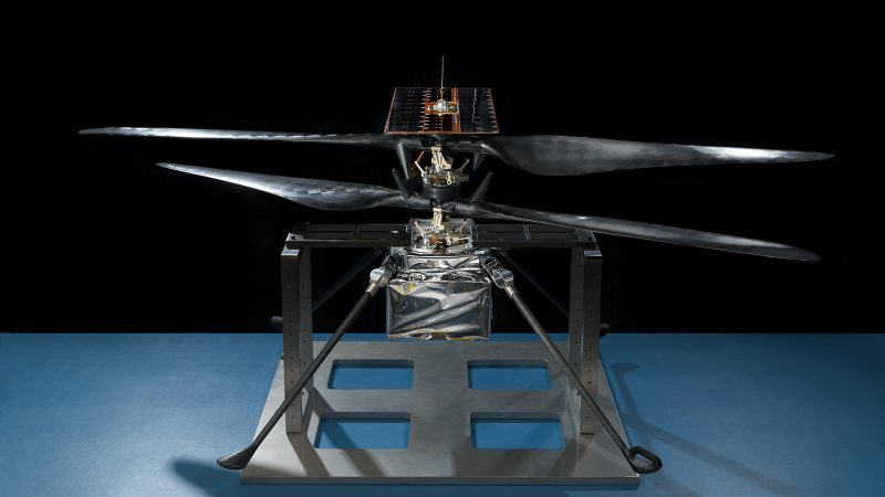 Helicopter propeller mounted on a metal stand framework, resting on a tabletop.
